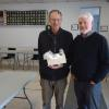 Mr. Schneider, the husband of the winner of one of the Heritage Fair door prizes, a basket of homemade preserves, with FNHA vice-president Fred White.